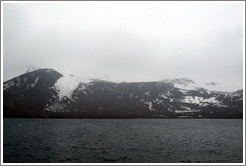The snow-covered volcanic mountains of Deception Island.