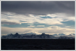Lenticular clouds hovering over mountains on the west coast of Graham Land.