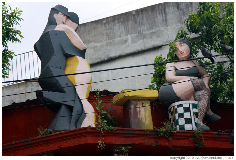 Sculptures on the roof of a building, depicting tango dancers and a longing spectator. Gral. Gregorio Ar? de Lamadrid, La Boca.