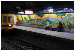 Young woman sitting in front of a mural called Paisajes de Espa?Mariano Moreno station, Subte (Buenos Aires subway).