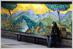 Young woman sitting in front of a mural called Paisajes de Espa�a, Mariano Moreno station, Subte (Buenos Aires subway).