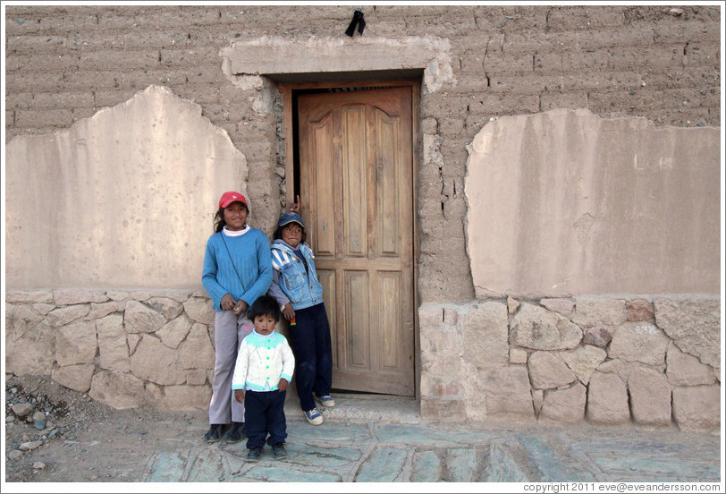 Three kids in a doorway.