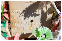 Headstone and plastic flowers for Santiago Ruca who passed away in August 1923, in a small miners' cemetery near La Polvorilla viaduct.