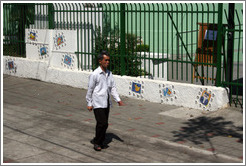 Man walking past tiled wall.
