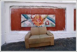Sofa in front of artwork on the wall surrounding the Cemit?o S?Paulo.