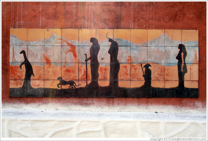 Artwork: silhouettes of a dinosaur, a feline with wheels for back legs, and people.  Wall surrounding the Cemit?o S?Paulo.