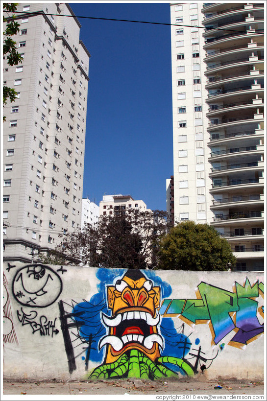 Graffiti: creature with pointed teeth and green tubes.  Buildings in the background.  Av. H?o Pellegrino at Rua Marcos Lopes.