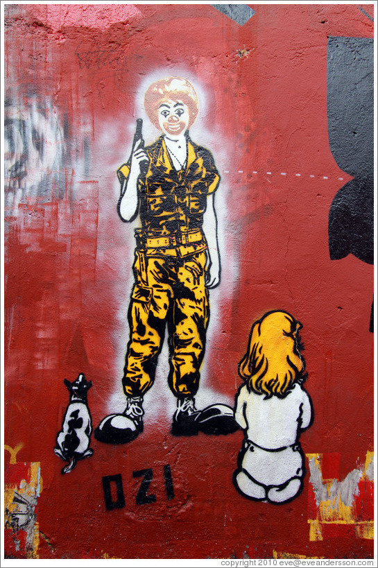 Graffiti: Ronald McDonald with a gun, with a dog and girl sitting in front of him.  Created by graffiti artist Ozi.  Villa Magdalenda neighborhood.  Alley between Rua Padre Jo?Gon?ves and
