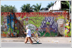 Graffiti: man with purple flames.  Woman walking in front.  Rua Nova Cidade.