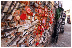 Lids attached to a wall.  Alley between Rua Padre Jo?Gon?ves and Rua Belmiro Braga.