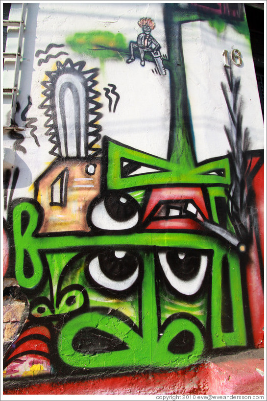 Graffiti: many green noses, a few eyes, a couple mouths, a cigarrette, a chainsaw, and a person sawing off the tree branch he's sitting on with a handsaw.  Villa Magdalenda neighborhood.  Rua Belmiro Braga and Rua Cardeal Arcoverde.