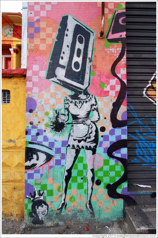 Graffiti: woman with a cassette tape head wearing a sexy maid outfit.  On her left, the head of a woman with a crown.  Villa Magdalenda neighborhood.  Rua Cardeal Arcoverde.