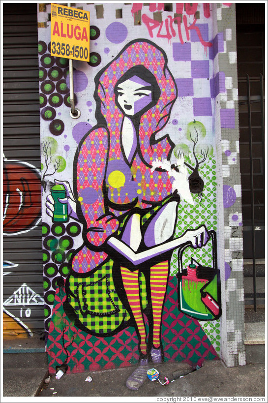 Graffiti: sitting woman with a hood, skirt, and striped socks, holding a bag.  Villa Magdalenda neighborhood.  Rua Cardeal Arcoverde.