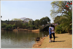 Couple kissing by a lake.  Parque do Ibirapuera.