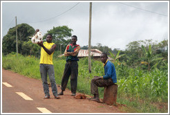 Three men selling goods at the side of the road, near the town of Bangangt