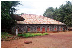 Building with satellite dish in a tribal compound.