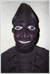 Wooden carving of a man with white eyes and smile.
