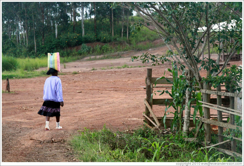 Girl carrying a bag on her head.
