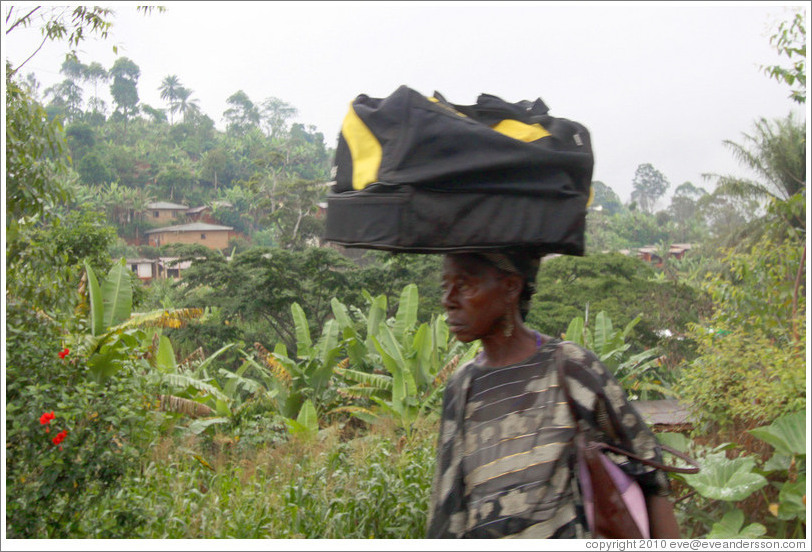 Woman carrying a duffel bag on her head.
