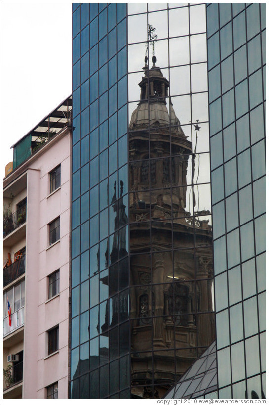 A tower of the Cathedral Metropolitana reflected in a modern building, Plaza de Armas.