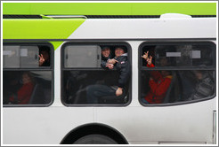 People on a bus making peace signs.