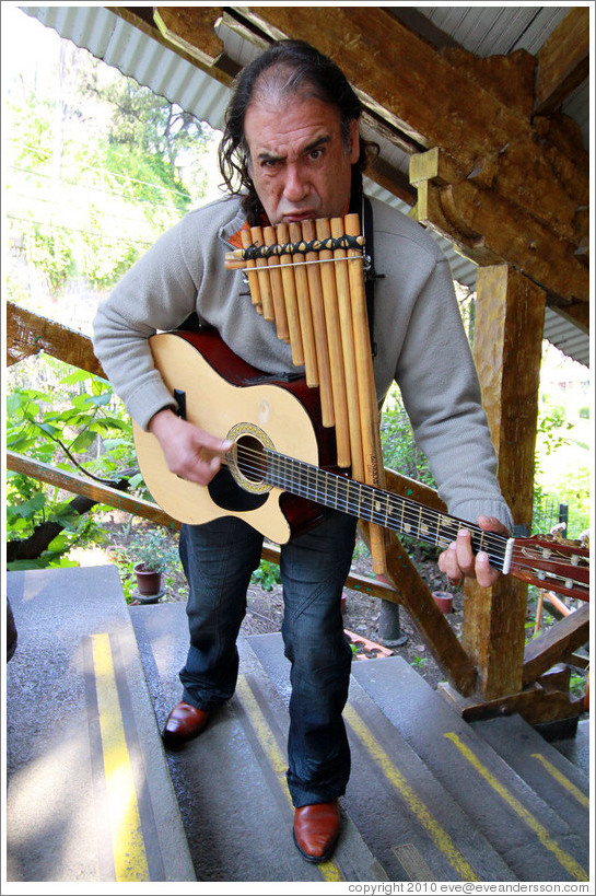 Musician playing pipes and guitar simultaneously, entertaining the funicular riders, Cerro San Crist?.