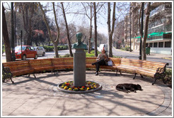 Man reading a newspaper on a bench, while a homeless dog sleeps near by.  Corner of Monjitas and Merced, Barrio Lastarria.
