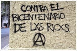 "Graffiti: Contra el Bicentenario de Lxs Ricxs.  (Against the Bicentennial of the rich.)  For some reason, the Os have been replaced with Xs in ""Los Ricos"" in this and other graffiti in the city.  San Martín, city center."