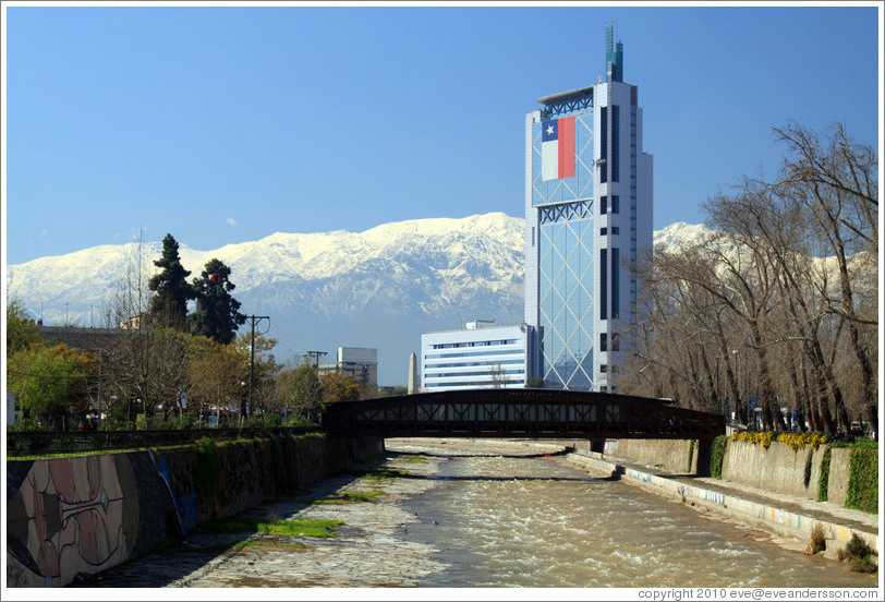 Looking east along the Mapocho River toward the mountains and a building with a Chilean flag.