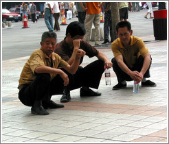 Men squatting.  Wangfujing Ave.