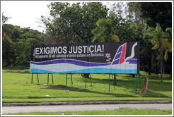 "Billboard on Avenida de la Independencia, saying: ""¡Exigimos justicia! Aniversario 36 del sabotaje al avió cubano en Barbados"" (""We demand justice! 36th anniversary of the sabotage of the Cuban airplane in Barbados"")."