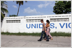 "Couple walking past a wall painted with the word ""Unidos"", part of ""Unidos, Vigilantes, y Combativos"" (""United, Vigilant, and Combative"")."