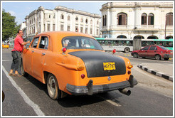 Driver beside his orange and black taxi, Avenida Salvador Allende (Carlos III).