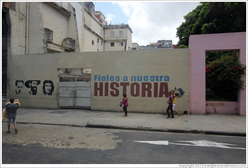"People walking past words painted on a wall saying ""Fieles a nuestra historia"" (""Faithful to our history""), Avenida Simon Bolivar (Calle Reina)."