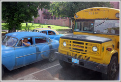 Blue cars and a repurposed school bus (now carrying adult passengers), corner of Calle Avenida de México Cristina and Calzada 10 de Octubre.