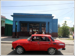 Red car in front of a blue building, Calzada 10 de Octubre.