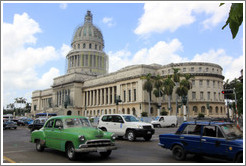 Green, blue and white cars in front of El Capitolio.