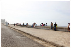 People sitting on the wall on the Malecón.