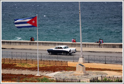 Cuban flag and a black and white car on the Malecón.
