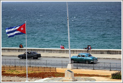 Cuban flag and black and blue cars on the Malecón.