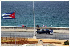 Cuban flag and a black car on the Malecón.