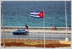 Cuban flag and a blue car on the Malecón.