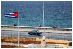 Cuban flag and a dark green car on the Malecón.