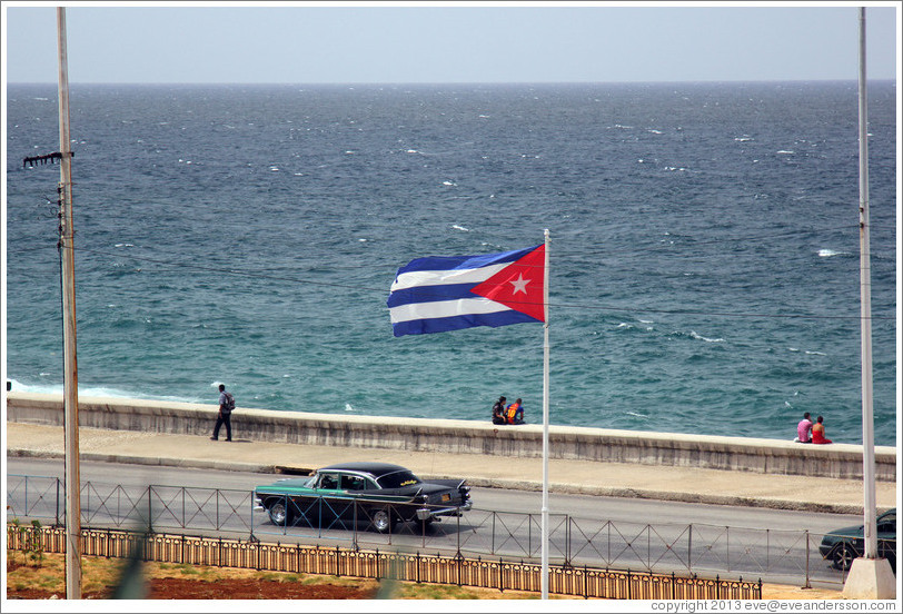 Cuban flag and a green and black car on the Malecón.