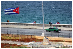 Cuban flag and a green car on the Malecón.
