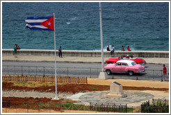 Cuban flag and pink and red cars on the Malecón.