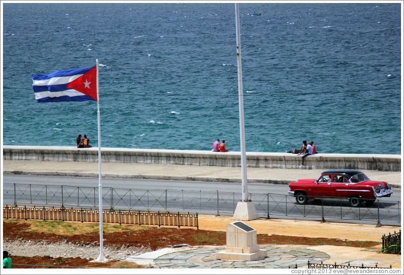 Cuban flag and a red car on the Malecón.
