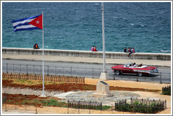 Cuban flag and a red convertible on the Malecón.
