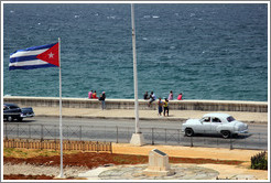 Cuban flag and a white car on the Malecón.