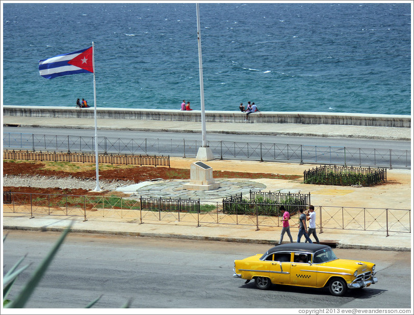 Cuban flag and a yellow and black taxi on the Malecón.